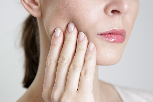 Woman with temporomandibular joint (TMJ) pain touching her jaw